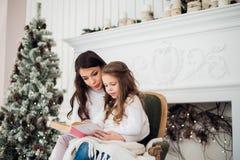 女孩和她的妈妈阅读书在圣诞节 库存图片