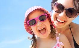 女孩和她的母亲在海边 库存图片