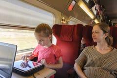 女孩和她的母亲火车的 免版税库存照片