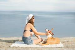 女孩和她的爱犬消费圣诞节假期在海边 免版税库存图片