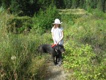女孩和她的狗在原野 库存照片