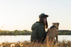 女孩和她的狗由湖日落的 免版税库存照片