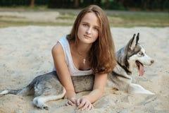 女孩和她的狗(多壳)走在秋天在城市公园 免版税库存照片