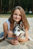 女孩和她的狗(多壳)走在秋天在城市公园 库存图片