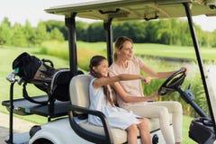 女孩和妇女一辆白色高尔夫车的 今后显示手的女孩 库存图片