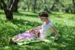 女孩和妇女在春天庭院 库存图片