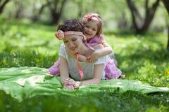 女孩和妇女在春天庭院 库存照片