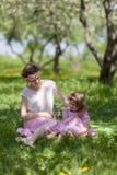 女孩和妇女在春天庭院 免版税库存照片