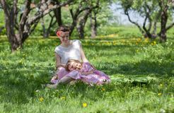 女孩和妇女在春天庭院 免版税图库摄影