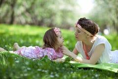 女孩和妇女在春天庭院 免版税库存图片