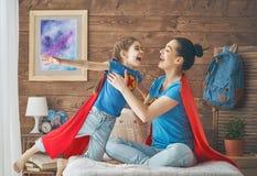 女孩和妈妈超级英雄服装的 库存图片