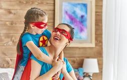 女孩和妈妈超级英雄服装的 库存照片