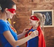女孩和妈妈超级英雄服装的 免版税库存照片