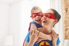 女孩和妈妈超级英雄服装的 免版税图库摄影