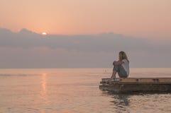 女孩和日出在海 库存图片