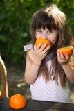 女孩和桔子 使用用桔子的女孩在一张桌上本质上 儿童果子女孩愉快的家庭小的桔子 愉快的女孩用在自然的果子 免版税库存图片