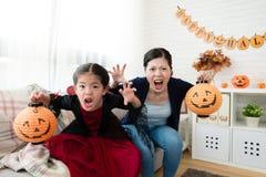 女孩和母亲假装恐怖面孔 库存图片