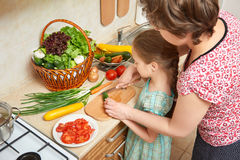 女孩和母亲在厨房、菜和新鲜水果里的砍黄瓜在篮子,健康营养概念 免版税库存图片