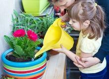 女孩和母亲浇灌的盆的花种植微笑 免版税库存图片