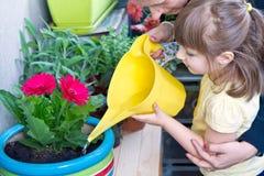 女孩和母亲浇灌的盆的花种植微笑 免版税图库摄影