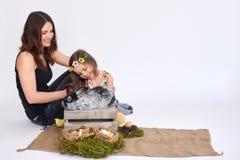女孩和母亲用一只灰色兔子 免版税库存照片