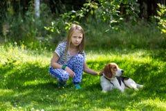 女孩和狗在夏天庭院里 库存图片
