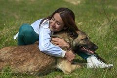 女孩和狗拥抱 免版税库存照片