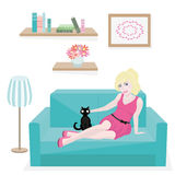 女孩和猫在长沙发 免版税库存照片
