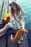 女孩和猫 与宠物的通信 照片在一个减速火箭的样式被设色 免版税库存图片