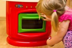 女孩和玩具厨房 库存图片