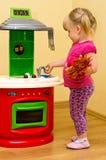女孩和玩具厨房 库存照片