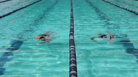 女孩和男孩严谨地在接踵而来的运动游泳竞赛的自由式被训练 活动公共 影视素材
