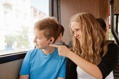 女孩和男孩在公共汽车上进来 库存照片