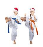 女孩和男孩在圣诞老人盖帽敲打今后踢腿 免版税库存照片
