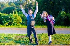 女孩和男孩在学校以后使用并且微笑 库存图片