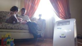 女孩和男孩在沙发和加热器使用在前景 股票视频