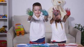 女孩和男孩在油漆的展示手 影视素材