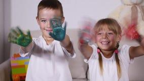 女孩和男孩在油漆的展示手 股票视频