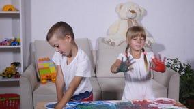 女孩和男孩在油漆的展示手 股票录像
