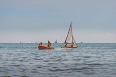 女孩和男孩在海的橡胶可膨胀的小船乘坐 男孩学会驾驶有风帆的一条小船 充气救生艇航行 库存图片