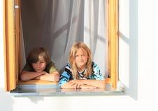 女孩和男孩在窗口后 免版税库存照片