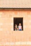 女孩和男孩在窗口里 免版税库存照片