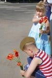 女孩和男孩在胜利天祝贺退伍军人并且要 库存照片