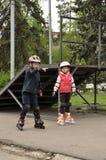 女孩和男孩在路辗滚动 免版税库存图片
