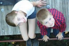 女孩和男孩坐桥梁 免版税库存照片