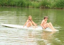 女孩和男孩坐海浪 免版税库存照片