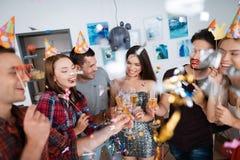 女孩和男孩庆祝生日 他们喝从玻璃的香槟并且获得乐趣 免版税库存图片