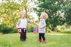 女孩和男孩微笑的笑握手和挥动美国和加拿大旗子,外部在公园 免版税库存照片