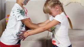 女孩和男孩抹上他们的在油漆的衬衣 影视素材