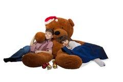 女孩和男孩拥抱与圣诞老人` s帽子的巨大的玩具熊在他的头 库存照片